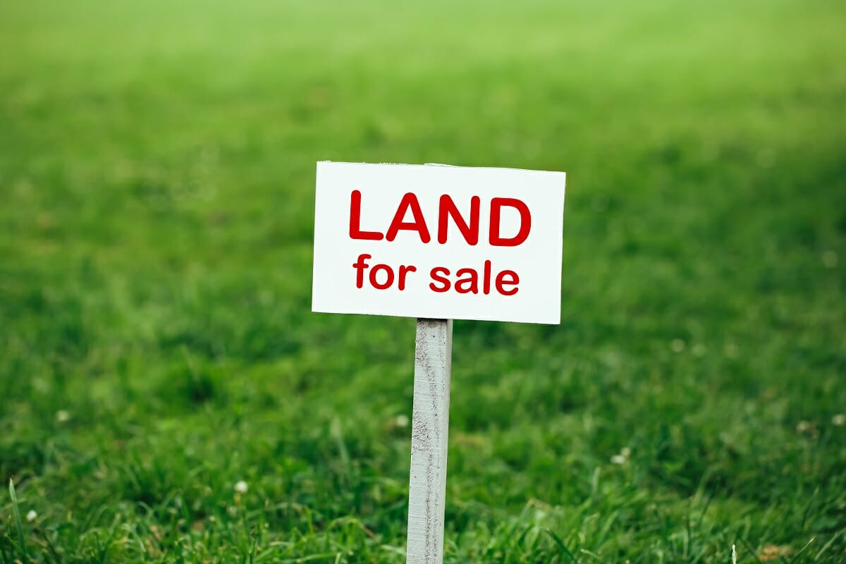 Image Of Vacant Land With A Land For Sale Sign In The Middle